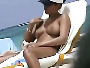 Voyeur cameraman finds beautiful brunette with fantastic boobs on the nude beach